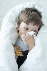 Little Boy blow her nose and get cold at home.