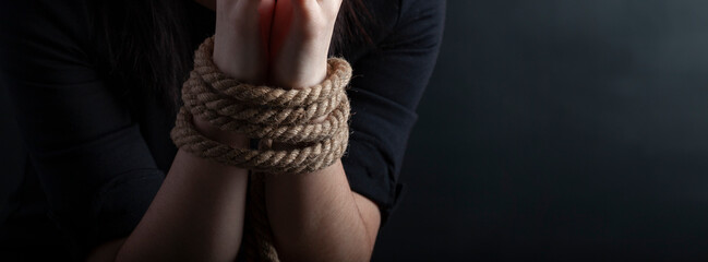 woman hands tied with a coarse rope close-up black background