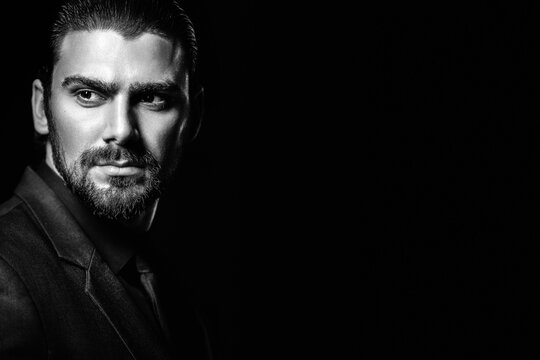 Business portrait of a white caucasian man in a black classic suit on a black background. Bearded man looks confident eyes.
