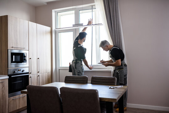 Young professional worker in uniform using tape measure, measuring window for installing blinds, while his aged colleague making notes. Construction and maintenance concept