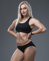 Studio portrait of a young pretty girl with a sporty physique on a studio background. Beautiful blonde in a top and sports shorts. Sportswear for athletics.