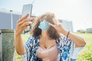 Young multiethnic woman wearing protective mask taking selfie with smartphone - Traveller woman outdoor taking photo on holiday with telephone - happiness, sociable, tourism concept