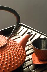 tetera japonesa y taza de hierro  color naranja sobre una mesa
