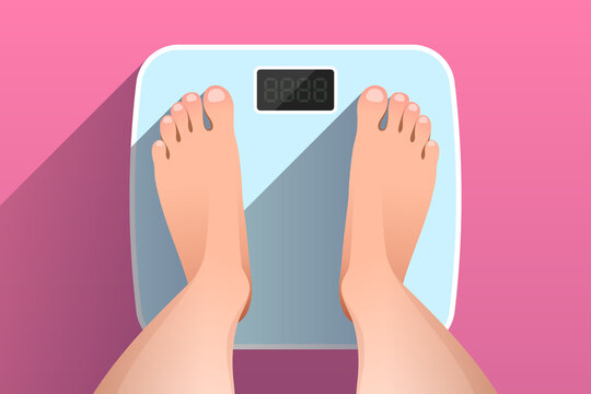 Top view of feet of woman standing on bathroom scales