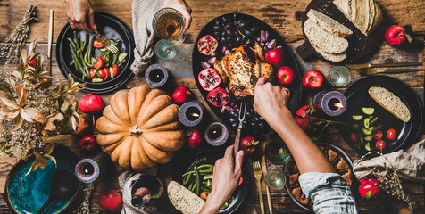 Thanksgiving table setting. Flat-lay of couple eating and drinking champagne at table with roasted chicken, vegetables, fig pie, fruit, candles over wooden table background, top view, wide composition