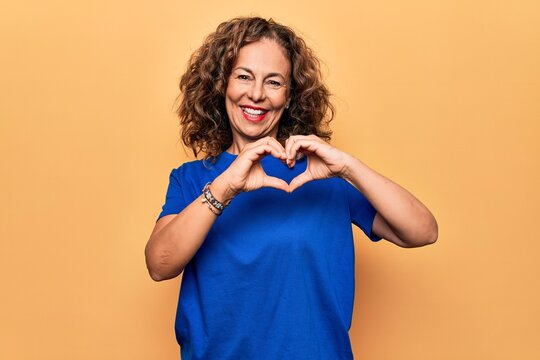 Middle age beautiful woman wearing casual t-shirt standing over isolated yellow background smiling in love doing heart symbol shape with hands. Romantic concept.