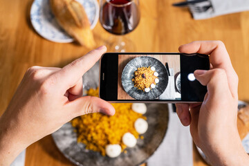 Man hand with smartphone photographing food at restaurant or cafe. High quality photo