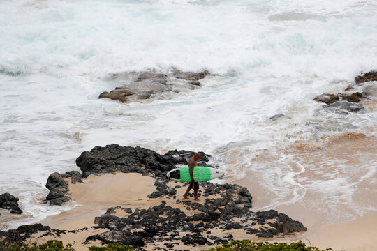 A surfer walks on Makapuu Beach in Waimanalo