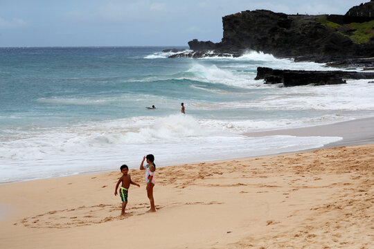 Two children play on Sandy Beach as Hawaii prepares for the arrival of Hurricane Douglas in Honolulu