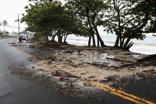 A police officer uses a plywood board to push beach debris off the road in Kaaawa, Hawaii, U.S. July 26, 2020, ahead of Hurricane Douglas