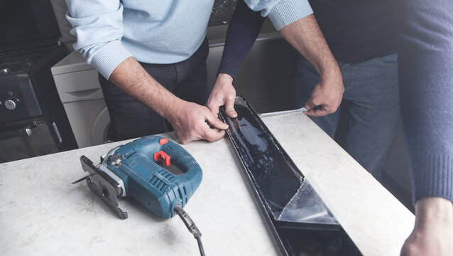 Workers measuring and cutting kitchen countertop using electric saw.