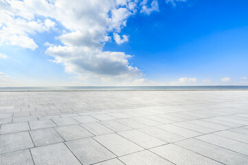 Empty square floor and river water under blue sky.