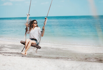 Young beautiful curly woman girl swinging and having fun on a swing on a tropical beach vacation and travel concept.