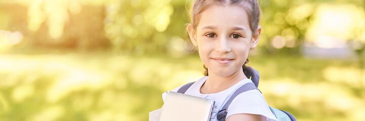 Young schoolgirl with backpack. Lifestyle going to classroom. Outdoor autumn park. Children learn smart. Street student. Happy preschool kid. Back to school