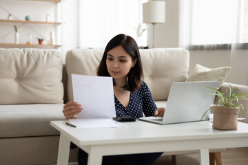 Young Vietnamese woman sit at desk use laptop mange household finances expenses consider bank documents, millennial Asian girl pay bills taxes on computer online, calculate expenditures at home