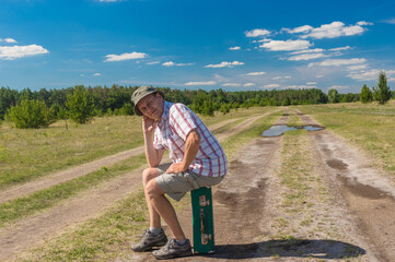 Portrait of mature Caucasian man sitting on an old green suitcase while hiking on a country road in Polavskaya oblast, Ukraine