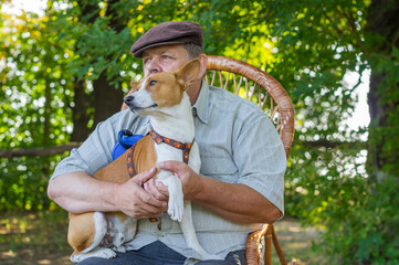 Portrait of cute basenji dog sitting on the hands of it's  senior master while resting in summer park