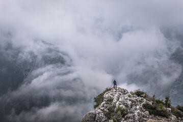 Man on a rock above Kadisha Valley also spelled as Qadisha, view from BLouza village in Lebanon