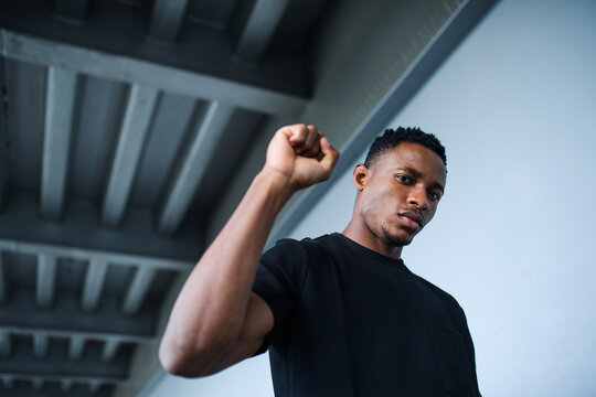 Black man with raised fist standing outdoors in city, black lives matter concept.