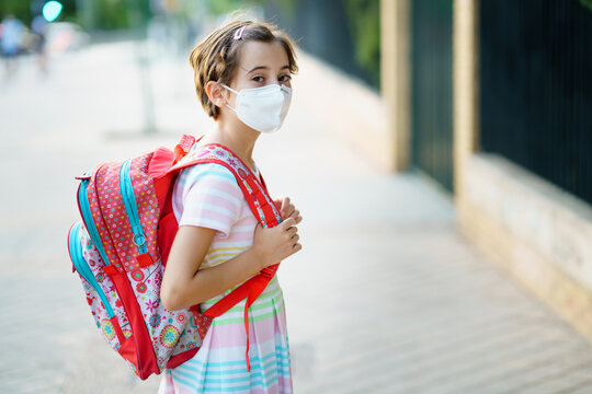 Nine years old girl goes back to school wearing a mask and a schoolbag.