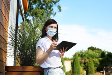 A businesswoman in a protective mask works online. Beautiful young woman writes on a digital tablet. Working outside the office.