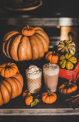 Pumpkin spice latte coffee drink topped with whipped cream and cinnamon in tall glasses among fresh pumpkins and persimmons over kitchen counter. Seasonal Autumn hot warming sweet drink