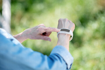 Elderly woman using a smartwatch to track her pulse