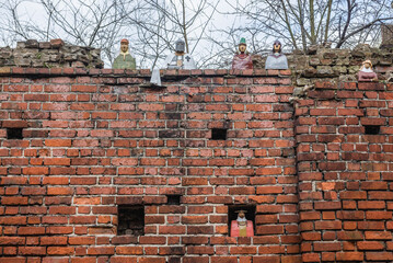 Ceramic statues of medieval citiziens placed on a historic wall in old part of Torun city in north central Poland