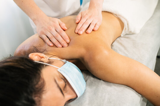 Caucasian woman receiving a physiotherapeutic shoulder massage while lying on a stretcher with a face mask