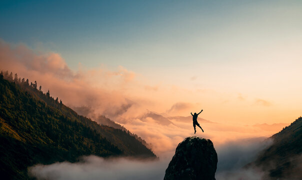 Silhouette of a Man jump and rises arms up on a peak. The happiness and excitement of beeing successful.