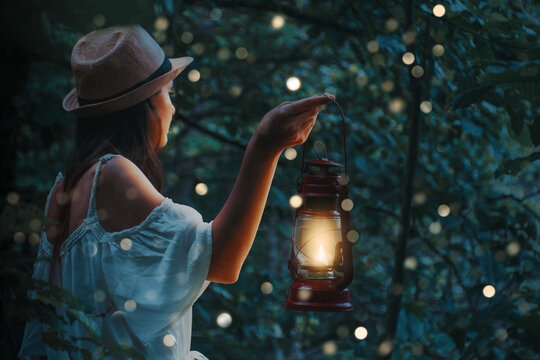 Beautiful woman in white dress holding a lantern in a forest with blurred glowings under the trees.