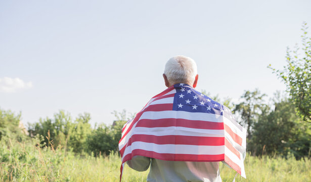 Patriotic senior man celebrates usa independence day on 4th of July with a national flag in his hands. Constitution and Citizenship Day. National Grandparents day