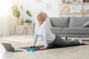 Online Yoga. Senior Woman Standing In Cobra Pose In Front Of Laptop