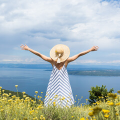 Rear view of young woman wearing striped summer dress and straw hat standing in super bloom of...