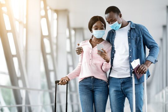 Checking Flight Information. Black couple wearing masks waiting for departure in airport