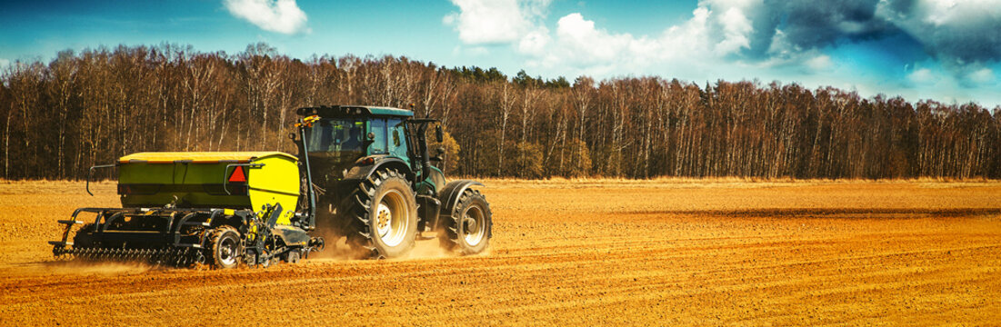 farmer with tractor seeding - sowing crops on agricultural field in spring. banner copy space