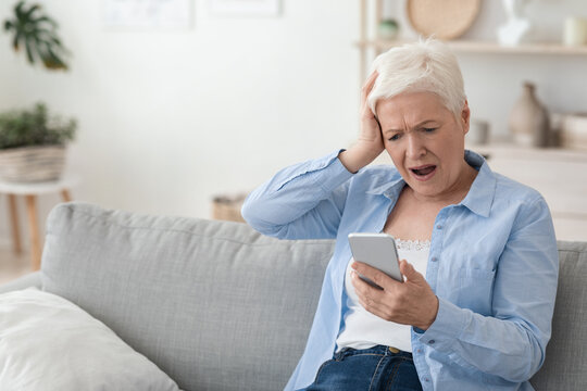 Mobile Scams Concept. Shocked Senior Woman Looking At Smartphone Screen In Frustration