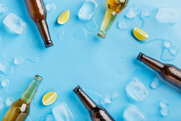 Dark and light glass beer bottles without labels with ice and pieces of lime on blue background Wall mural