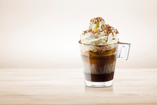 Cup of coffee with whipped cream, milk foam and chocolate chips on wooden table.