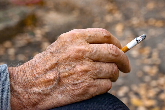 Hand of very old man with cigarette