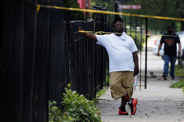 A man stands behind Chicago police crime scene tape, at the scene of a gun shooting, on the South Side of Chicago