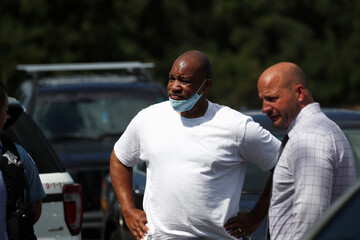 A man with a protective face mask stands with a law enforcement investigator at a crime scene, where a 37-year-old man riding a bicycle was shot and pronounced dead at the hospital according to local media reports, on the West Side of Chicago