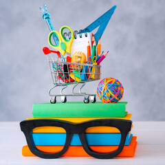 Colorful school supplies shopping basket gray background with a copy text space. A stack of books with colorful covers frame glasses.