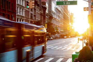 Fotomurales - New York City bus driving through the intersection of 23rd Street and 5th Avenue in Manhattan with the light of sunset shining between the skyline buildings