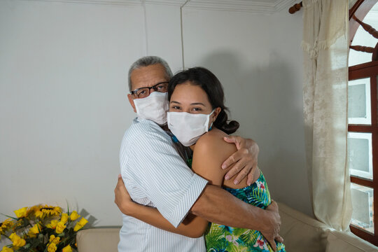 Young daughter with mask hugs her father