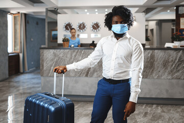 African man hotel guest with suitcase wearing protective mask to protect from coronavirus