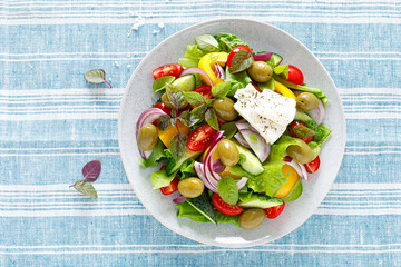 Greek salad. Fresh vegetable salad of cucumbers, tomatoes, olives, onion, bell pepper, feta cheese, lettuce and herbs and dressed with salt, pepper and olive oil. Popular greek Horiatiki salad