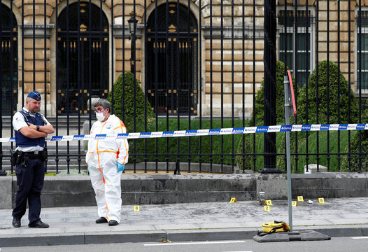 A police officer and a forensic investigator are seen in front of the Belgian Parliament after a suspect threw a Molotov cocktail, according to local media, in Brussels