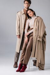 full length view of young couple in trendy autumn clothes looking at camera on grey