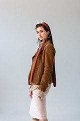 attractive, fashionable girl in suede jacket looking at camera isolated on grey